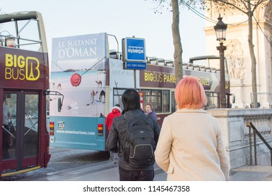 Paris, France, Europe. Mar 2018: Cityscape of tourist on Champs Elysees road at Big Bus station near Arc de Triomphe (Arch of Triumph) at l'Etoile. Travel to famous Paris landmarks on a winter