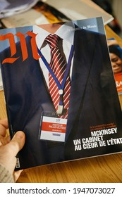 Paris, France - Feb 13, 2021: POV male hand holding M magazine Le Monde with cover breaking story of McKinsey American worldwide management consulting firm relations with Elysee palace