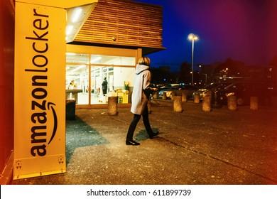 PARIS, FRANCE - FEB 15, 2017: Customer leaving Amazon locker orange delivery package locker at dusk - Amazon Locker is a self-service parcel delivery service offered by online retailer Amazon.com.