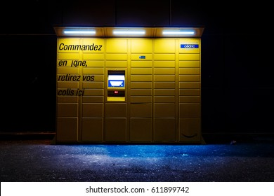PARIS, FRANCE - FEB 15, 2017: night view over an Amazon locker orange delivery package locker at dusk - Amazon Locker is a self-service parcel delivery service offered by online retailer Amazon.com
