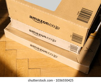 PARIS, FRANCE - FEB 21, 2018: View from above of three Amazon Prime Japan boxes stack on wooden background