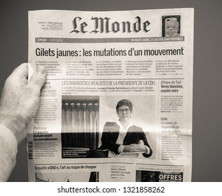 Paris, France - Feb 22, 2019: Man hand holding against gray background Le Monde newspaper with portrait of Annegret Kramp-Karrenbauer and article about Yellow vests protest