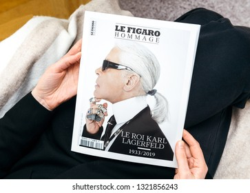 Paris, France - Feb 23, 2019: Pov woman reading French Le Figaro Hommage Tribute magazine covering Karl Lagerfeld death, iconic fashion designer died aged 85