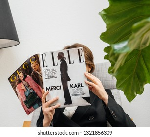 Paris, France - Feb 23, 2019: Woman reading French Elle magazine covering Karl Lagerfeld death, iconic fashion designer died aged 85 and was creative director at Chanel Fendi fashion houses