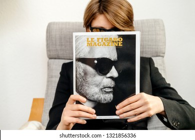 Paris, France - Feb 23, 2019: Woman reading French Le Figaro magazine covering Karl Lagerfeld death, iconic fashion designer died aged 85 and was creative director at Chanel Fendi fashion houses