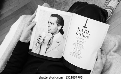 Paris, France - Feb 23, 2019: Woman reading French magazine covering Karl Lagerfeld death, iconic fashion designer died aged 85 and was creative director at Chanel Fendi fashion houses monochrome
