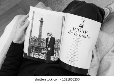 Paris, France - Feb 23, 2019: Woman reading French Le Figaro covering Karl Lagerfeld death, iconic fashion designer died aged 85 and was creative director Chanel Fendi fashion houses - Icone de la