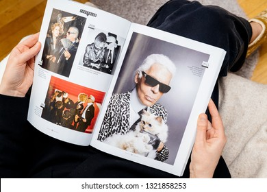 Paris, France - Feb 23, 2019: Woman reading French magazine Le Figaro covering Karl Lagerfeld death, iconic fashion designer died aged 85 article about his cat Choupette