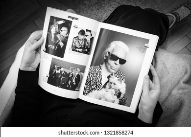 Paris, France - Feb 23, 2019: Woman reading French Le Figaro magazine covering Karl Lagerfeld death, iconic fashion designer died aged 85 article about his cat Choupette - black and white