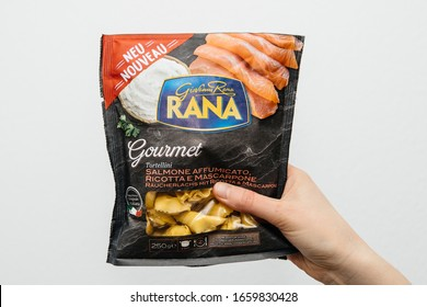 Paris, France - Feb, 25, 2020: man hand holding against white background package of Giovanni Rana Gourmet Tortellini with smoked salmon taste