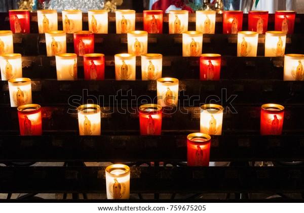 PARIS, FRANCE - FEBRUARY 1, 2017: Rows of firing lit votive candles inside Notre Dame de Paris, France.