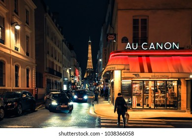 Paris, France - February 10, 2018: Typical view of Parisian street. Architecture and landmark of old town. Cozy and beautiful historic city. French city street scene, buildings exterior, cafe, people.