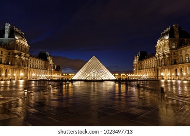 Paris, France - February 11, 2018:  view of the Louvre Museum (Musee du Louvre) and the famous pyramid after rain