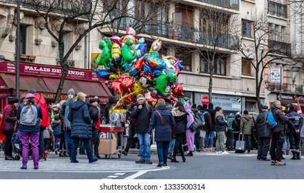 Paris, France - February 11,2018: People waiting in the street in front of a stand with colorful balloons during the Carnaval de Paris 2018.