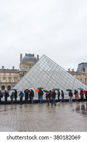 PARIS, FRANCE - FEBRUARY, 13, 2016: Louvre Museum on the stormy rainy day in a winter season, people with the umbrella stand in line waiting to get inside the museum.