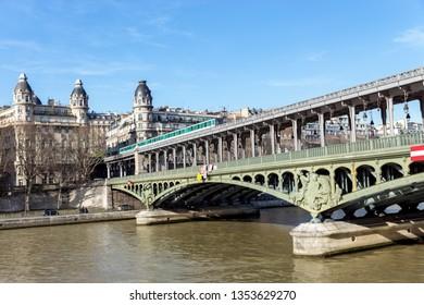 Paris, France - February 13, 2019: Metro traffic on Pont Bir-Hakeim (Passy viaduc) with view over Passy station buildings - Paris, France