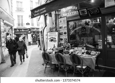PARIS, FRANCE - FEBRUARY 14, 2019: Fondue Savoyarde and Raclette displayed (to attract customers) in typical traditional restaurant in Latin Quarter. Senior couple passing nearby. Black white photo.
