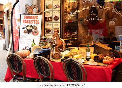 PARIS, FRANCE - FEBRUARY 14, 2019: Fondue Savoyarde and Raclette displayed (to attract customers) in typical traditional restaurant in Latin Quarter. Senior couple reflection window. Urban scene.