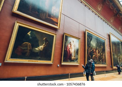 PARIS, FRANCE - FEBRUARY 15, 2018: Tourists visit art gallery in Louvre Museum. Louvre Museum is one of the largest and most visited museums worldwide
