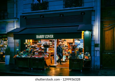 Paris, France - February 15, 2018: Man in coat and hat in fruits and veggies shop. Grocery store on pedestrian french street in spring evening. View to typical facade of parisian old building.