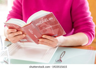 Paris, France - February 15, 2021 - Woman reading Red Michelin guide book which reviews restaurants.