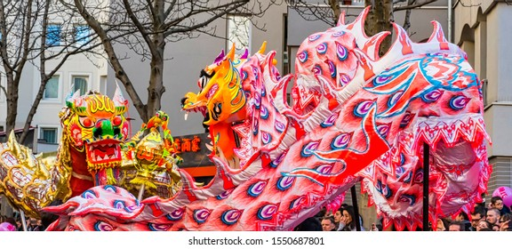 PARIS, FRANCE - FEBRUARY 17, 2019. Last day of the chinese new year celebration festival in street. Dance of colorful pink dragon in the street during the parade festival. Traditional celebration.