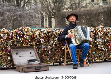 PARIS, FRANCE - FEBRUARY 18, 2014: Accordion player on the Pont de l'Archeveche (Archbishop's Bridge) at the Notre-Dame in Paris, France, on February 18, 2014
