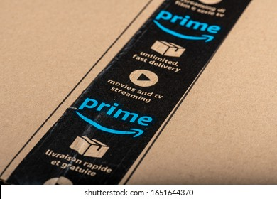 Paris, France - February, 20, 2020  : Amazon Prime logotype printed on cardboard box security scotch tape. Amazon Prime is a service from Amazon which delivers parcels in 1 day.