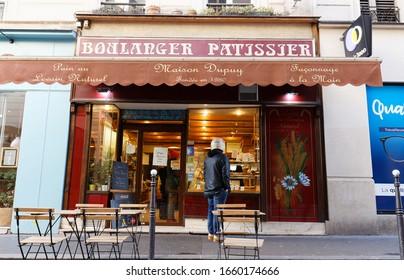 Paris, France- February 26 , 2020 : The traditional French bakery shop Maison Dupuy located at Cadet street in Paris, France. Inscription in French : Baker, Confectioner, natural sourdough bread,House