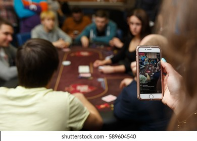 PARIS, FRANCE - FEBRUARY 27, 2017: Hand holding Iphone and using Instagram application streaming online some poker game tournament. Focus on mobile phone/