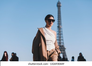 Paris, France - February 27, 2019: Street style outfit - Fashionable girl posing in front of Eiffel Tower during Paris Fashion Week - PFWFW19
