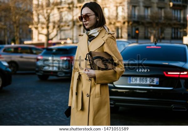 PARIS, FRANCE - FEBRUARY 27, 2019: Beatrice Gutu wears sunglasses, a yellow trench coat, brown Loewe bag outside ROCHAS show, during Paris Fashion Week Womenswear Fall/Winter 2019/2020.