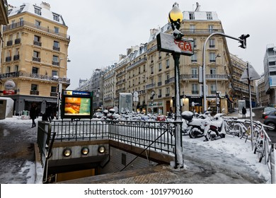 Paris, France - February 7, 2018: Parisian metro sign and bicycle covered with snow