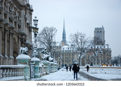 PARIS, FRANCE - FEBRUARY 7, 2018: Parisians going to work in rare snowy winter morning through Hotel de ville (city hall) square covered with snow. Notre Dame cathedral at background.