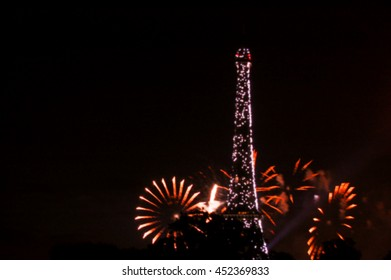 Paris, France. Fireworks near Eiffel Tower during celebrations of French national holiday (Bastille Day, on 14 July). Blurred toned photo.