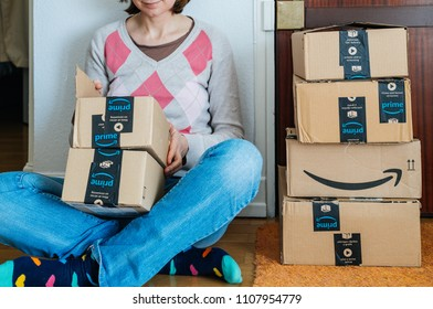 PARIS, FRANCE - JAN 13, 2018: Stack of Amazon Prime packages delivered to a home door smiling woman begin to unbox the cardboard boxes