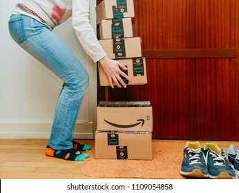 PARIS, FRANCE - JAN 13, 2018: Woman lyft the Amazon Prime packages delivered to a home door