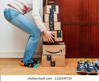 PARIS, FRANCE - JAN 13, 2018: Stack of Amazon Prime packages delivered to a home door woman trying to lift heavy boxes to do the unboxing