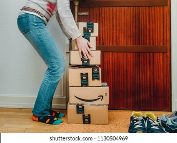 PARIS, FRANCE - JAN 13, 2018: Stack of Amazon Prime packages delivered to a home door woman trying to lift heavy boxes near the door