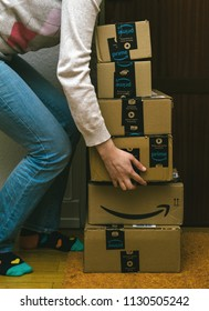 PARIS, FRANCE - JAN 13, 2018: Woman and Amazon Cardboard boxes lifted by woman near apartment door