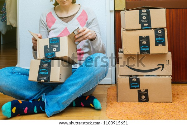 PARIS, FRANCE - JAN 13, 2018: Stack of Amazon Prime packages delivered to a home door woman unboxing one of the small boxes. Amazon is the largest internet based retailer in the United States