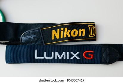 PARIS, FRANCE - JAN 14, 2015: New Nikon DSLR and Panasonic G Mirrorless camera straps on white background