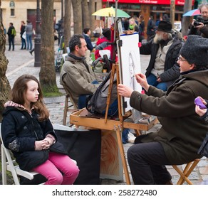 PARIS, FRANCE - JAN 17, 2015: Unidentified artist drawing a portrait of the tourist at Place du Tertre, Montmartre. Place du Tertre is now an open-air workshop with its 288 official painters.