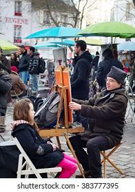 PARIS, FRANCE - JAN 17, 2015: Unidentified artist drawing a portrait of the tourist at Place du Tertre, Montmartre. Place du Tertre is now an open-air workshop with its 288 official painters.