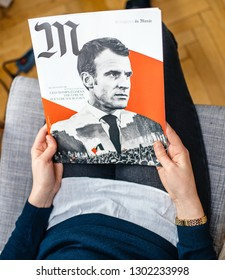 Paris, France - Jan 2, 2019: Woman reading M le magazine du monde with controversial cover featuring French presidient Emmanuel Macron with a photo collage of Macron and the Yellow Vest protesters