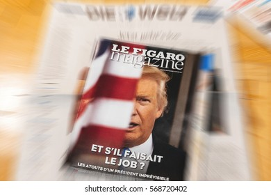 PARIS, FRANCE - JAN 21, 2017: Man holding Le Figaro above major international newspaper journalism featuring portrait of Donald Trump inauguration as the 45th President of the United States