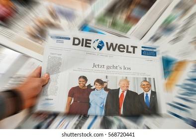 PARIS, FRANCE - JAN 21, 2017: Man holding Die Welt above major international newspaper journalism featuring headlines with Donald Trump, Barack Obama, Melania Trump and Michele Obama inauguration