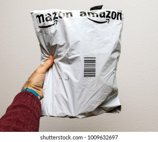 PARIS, FRANCE - JAN 23, 2018: Man holding against white background a plastic parcel delivery of Amazon package containing clothes or shoes