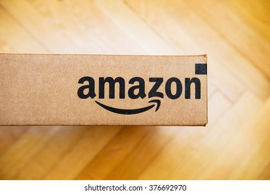 PARIS, FRANCE - JAN 28, 2016: Amazon logotype printed on cardboard box side, seen from above on a wooden floor. Amazon Inc is the an American electronic e-commerce company