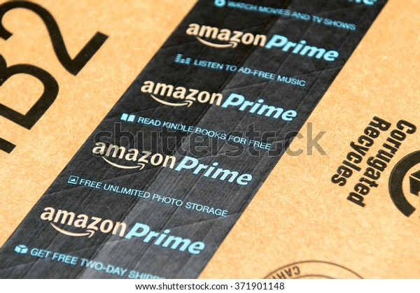 PARIS, FRANCE - JAN 28, 2016: Amazon Prime logotype printed on cardboard box security scotch tape. Amazon Prime is a service from Amazon which delivers parcels in 1 day, streams unlimited music